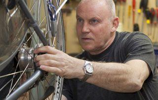 Meneer repareert de fiets van een gast
